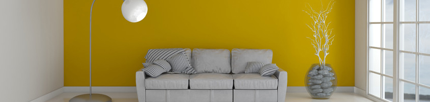 Sofa and lamp in yellow room with window.